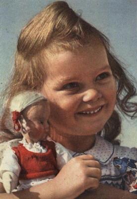 Улыбающаяся девочка с куклой