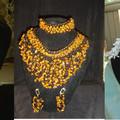Это очень красивое изделие.  Сделанное из бисера двух цветов и камня янтаря.  В комплекте ожерелье, фенечка...