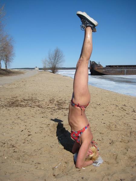 стойка на голове на песчаном берегу ледяной Волги